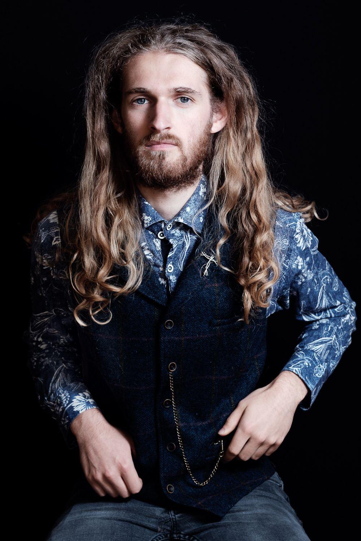 portrait of long haired male musician in waistcoat