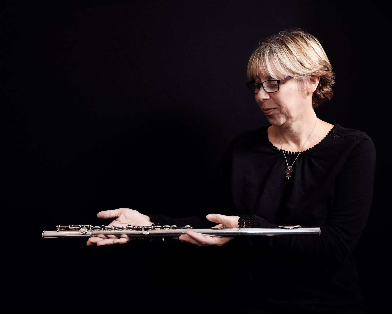 portrait of woman holding silver flute against black backdrop