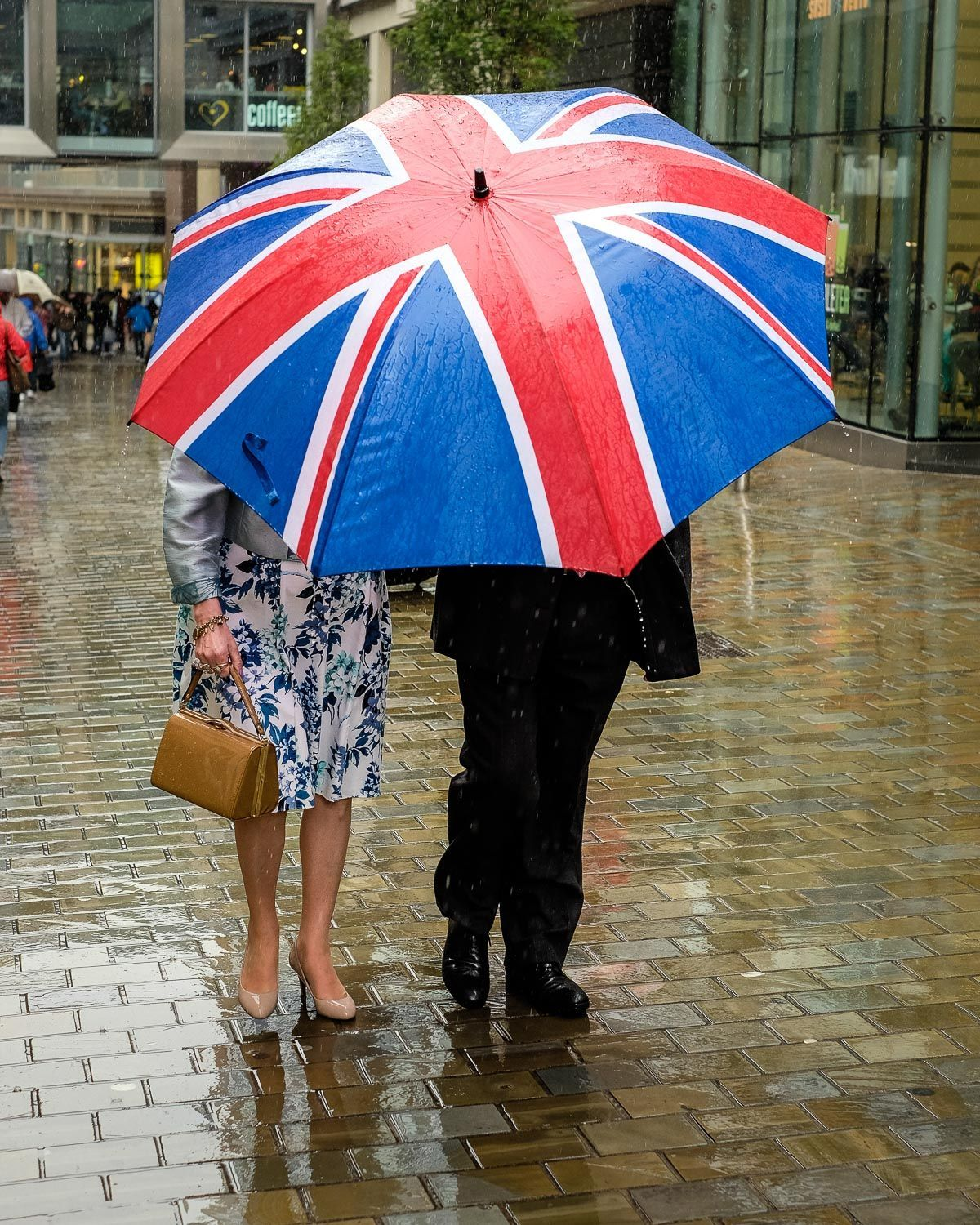 street photo of couple obscured by large union flag umbrella