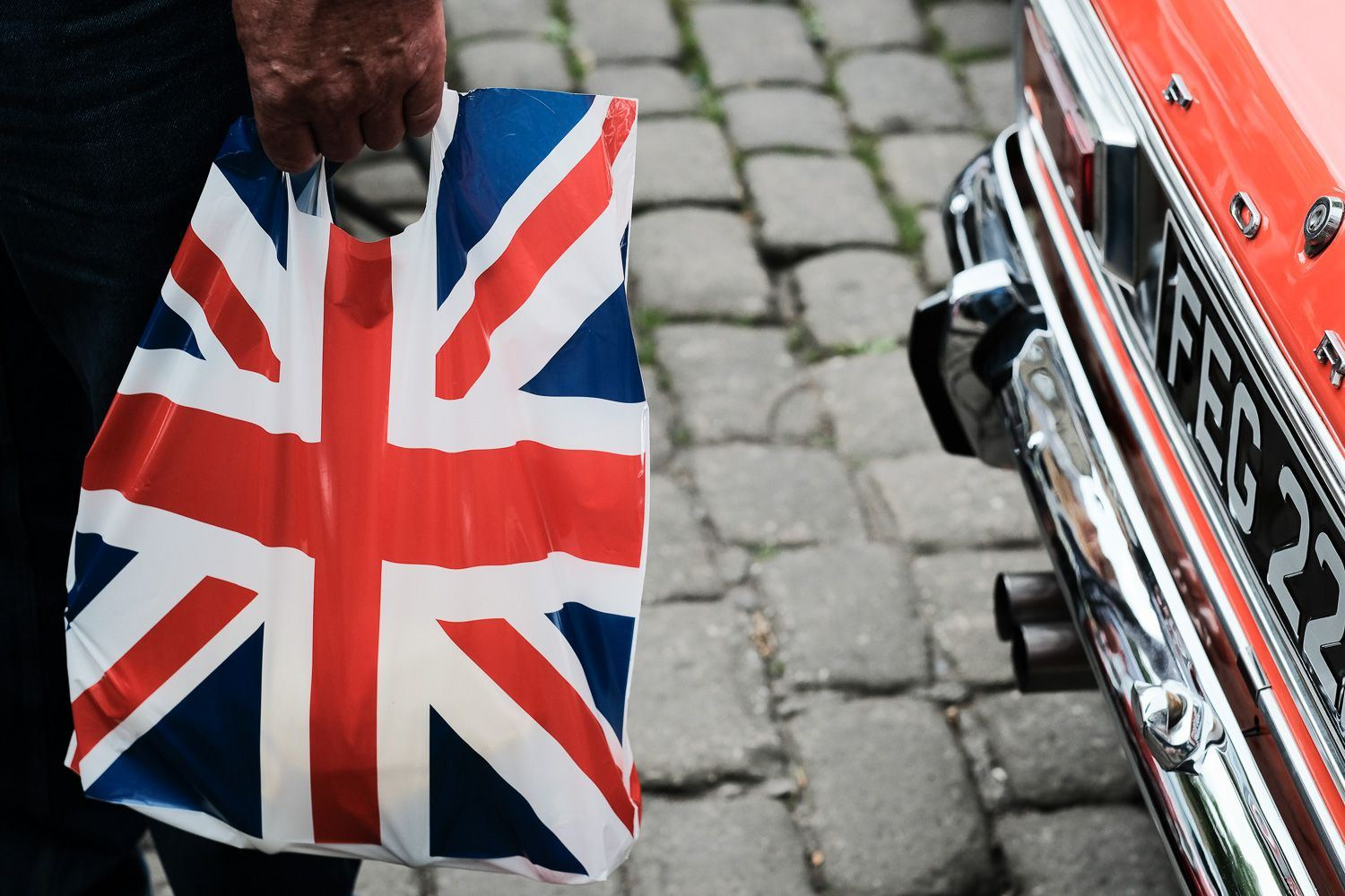 street photo of man carrying union flag carrier bag