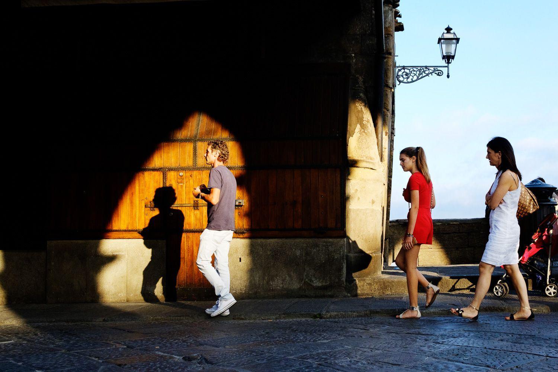 street photo of man walking into light followed by two women