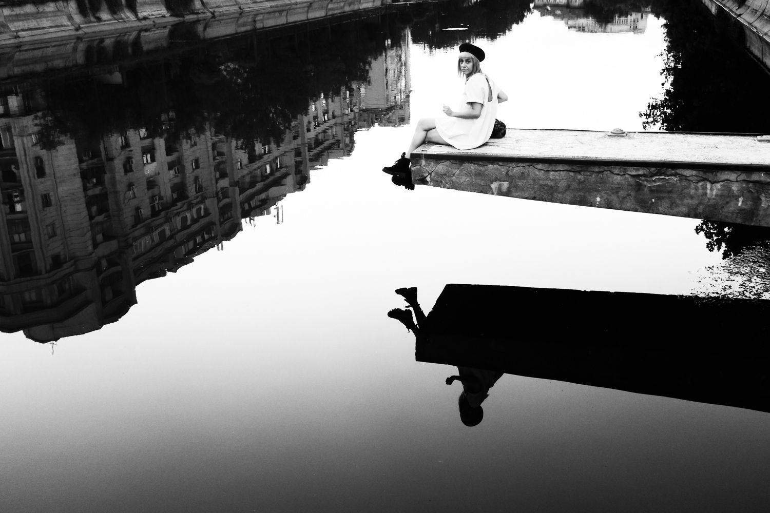 street photo of woman sitting on jetty with reflection in water